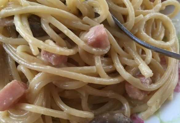 Spaghetti noodles, ham, and mushrooms swim in a creamy garlic sauce made from cream and eggs and cheese.